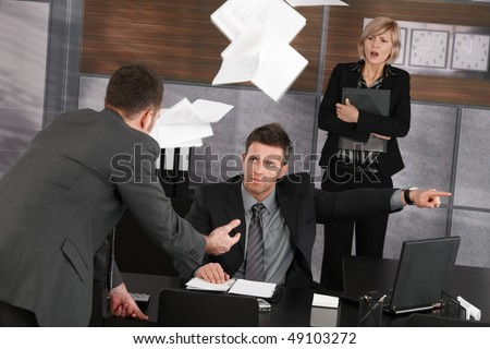Angry boss firing employee, showing door. Papers flying in air, scared secretary standing in background. - stock photo