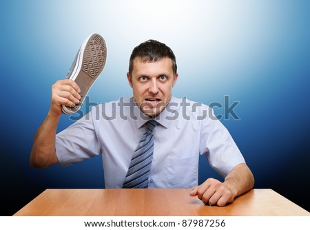 Angry boss knocks shoes on the table - stock photo
