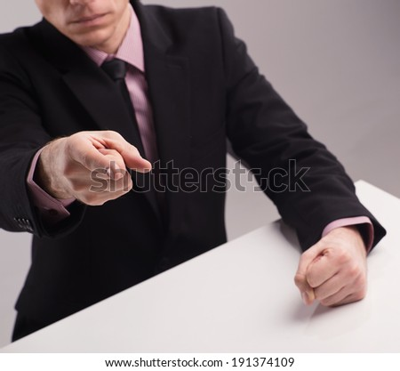 Angry boss. Man in suit banging his fist on the desk - stock photo