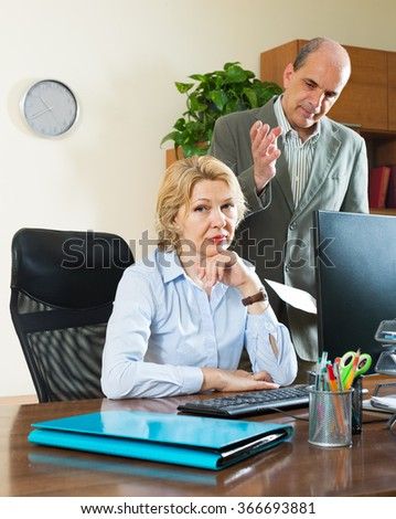 Angry boss screaming at his mature female assistant - stock photo