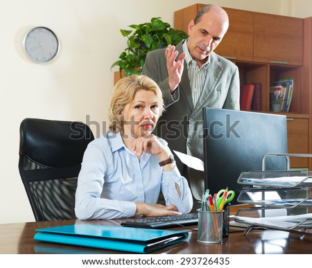 Angry boss screaming at his mature female assistant in office