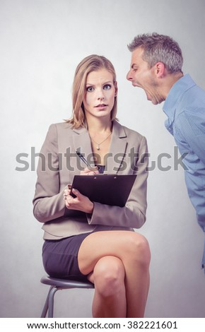 Angry boss screaming to his employer woman and she is surprised and shocked - stock photo