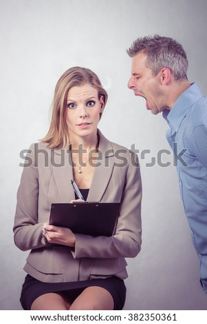 Angry boss screaming to his employer woman and she is surprised and shocked. isolated on white background.  - stock photo