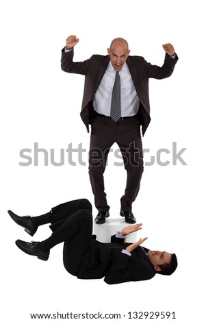 Angry boss shouting at employee laying on the floor - stock photo