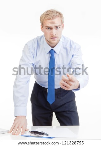 angry boss standing behind desk, gesticulating, accusing, blaming