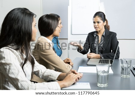 Angry boss talking with her team during a meeting. Indian business woman. - stock photo
