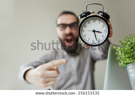 Angry boss with beard and glasses holds alarm clock screaming on camera