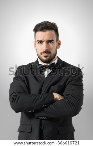 Angry bossy man in tuxedo with crossed arms intense looking at camera. Portrait over gray studio background.  - stock photo