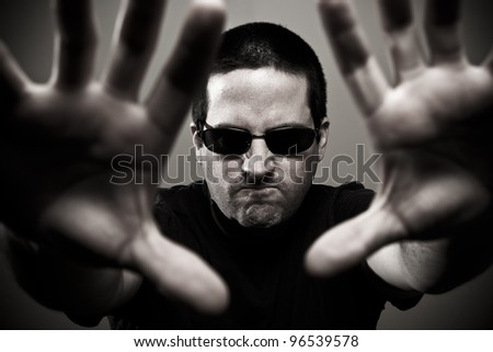 Angry bouncer reaches forward - focus on bouncer's face - stock photo