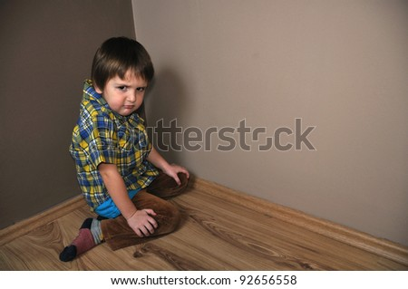 Angry boy in corner - stock photo