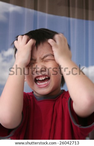 Angry boy in red tee holding his head shouting angrily - stock photo