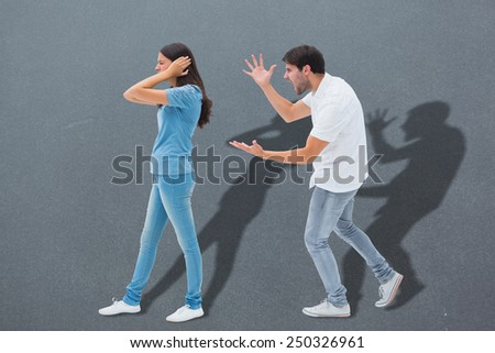 Angry boyfriend shouting at girlfriend against grey - stock photo