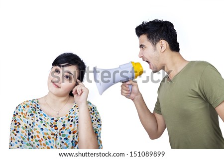 Angry boyfriend shouting at his girlfriend using megaphone on white background - stock photo