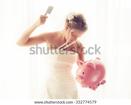 Angry bride with knife in hand about to smash piggy bank  - stock photo
