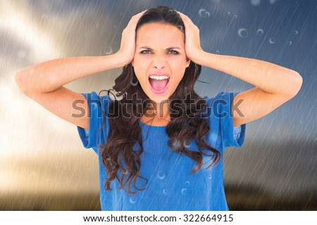 Angry brunette shouting at camera against cloudy sky