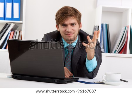 Angry business man hand gesture sitting at desk in office, portrait of young handsome businessman looking at camera, concept of executive yelling, conversation problem communication crisis - stock photo