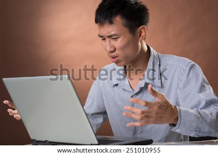 Angry business man of Chinese sitting on chair and looking at laptop on desk in studio. - stock photo