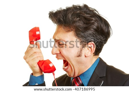 Angry business man screaming loudly into a red phone receiver - stock photo