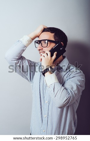 Angry business man screaming on cell mobile phone, portrait of young handsome businessman isolated over a gray background, concept of executive yelling, conversation problem communication crisis - stock photo
