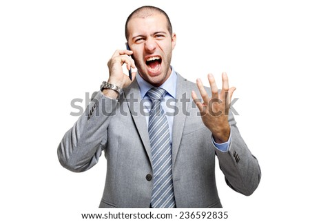 Angry business man screaming on mobile phone - stock photo