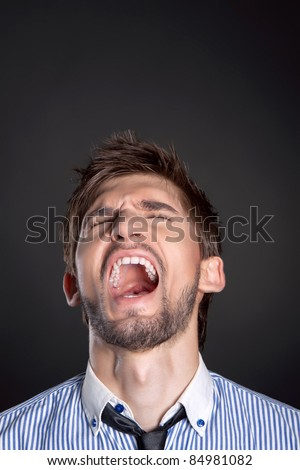 Angry business man screaming over black background - stock photo
