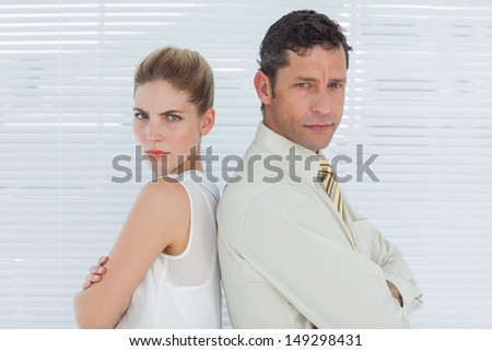Angry business team posing back to back in bright office - stock photo