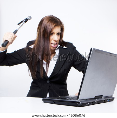 angry business woman about to demolish her laptop with a hammer - stock photo