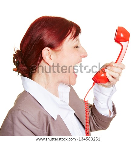 Angry business woman screaming loudly in a red phone receiver - stock photo