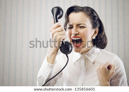 Angry Business Woman shouting into telephone - stock photo