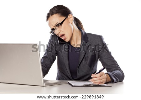 Angry business woman working on a laptop, talking on the phone and write in notebook