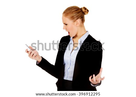 Angry business woman yelling to the mobile phone - stock photo