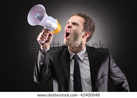 Angry businessman announcing via loudspeaker - stock photo
