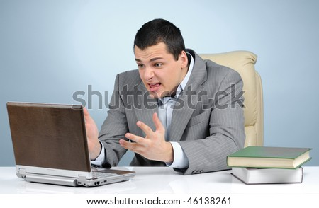 Angry businessman at work on gray background