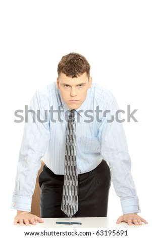 Angry businessman behind the desk - stock photo