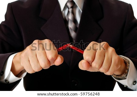 Angry businessman breaking pencil by hands - stock photo