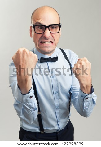 angry businessman clenched teeth shakes his fist. Gray background - stock photo