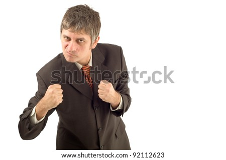 Angry businessman in aggressive boxing pose isolated on white background - stock photo