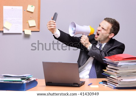 Angry businessman in an office, shouting on a megaphone, holding a mobile phone in the hand