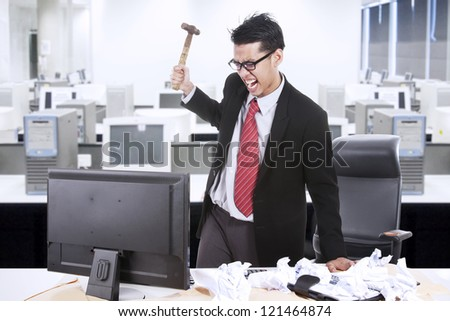 Angry businessman is about to throw a hammer at his computer in the office