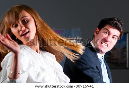 angry businessman is slapping across the businesswoman's face - stock photo