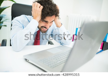 Angry businessman looking at his computer - stock photo