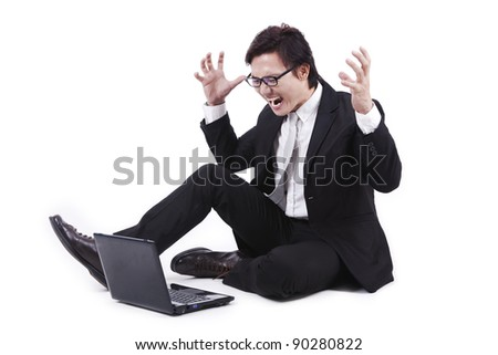 Angry businessman looking at his laptop isolated on white - stock photo