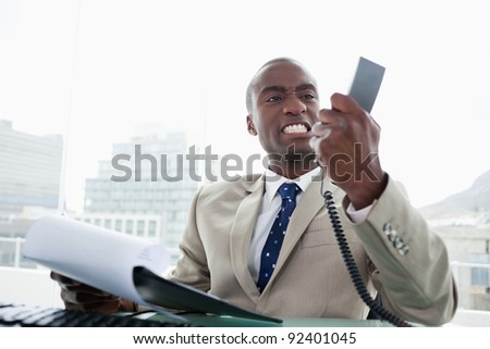 Angry businessman looking at his phone handset in his office - stock photo