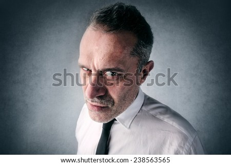 Angry businessman looking straight into the camera  - stock photo
