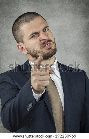 Angry Businessman pointing at you - stock photo