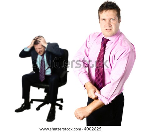 Angry businessman ready for a fist fight, rolling up his sleeve with colleague in background appearing stressful and upset. - stock photo