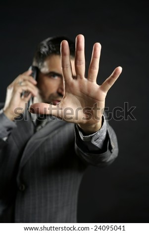 Angry businessman saying stop with hand,talking to a mobile phone - stock photo