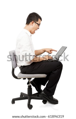 Angry businessman screaming against a laptop on the chair