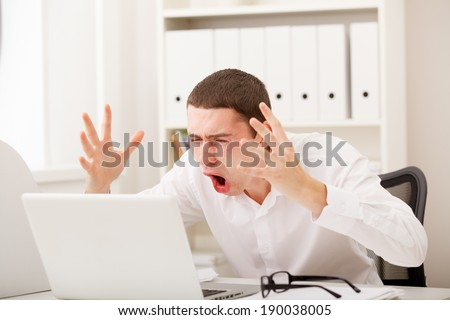 Angry businessman screaming against laptop in office - stock photo