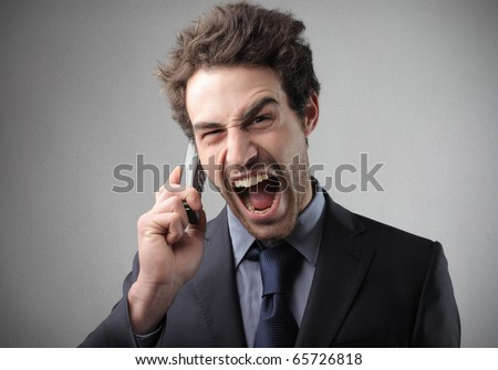 Angry businessman screaming at telephone - stock photo